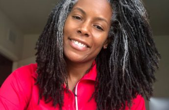 Photo of woman in a red shirt with sisterlocks that are grey towards the scalp and black/brown on the bottom
