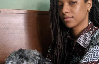 girl with locs with wooden bed hedboard and green wall in background. yorkie poo dog sitting her lap