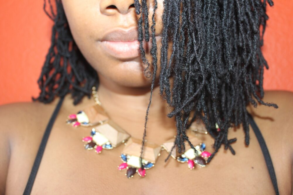 woman with half of her head and locs showing. has necklace on. article is about traction alopecia with locs.