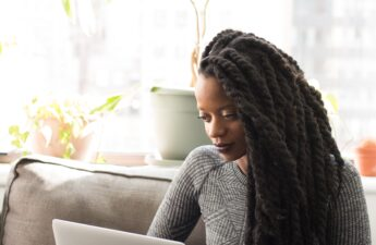 Black woman with marley braid extensions researching on her laptop. Meant to represent woman researching questions to ask a loctician