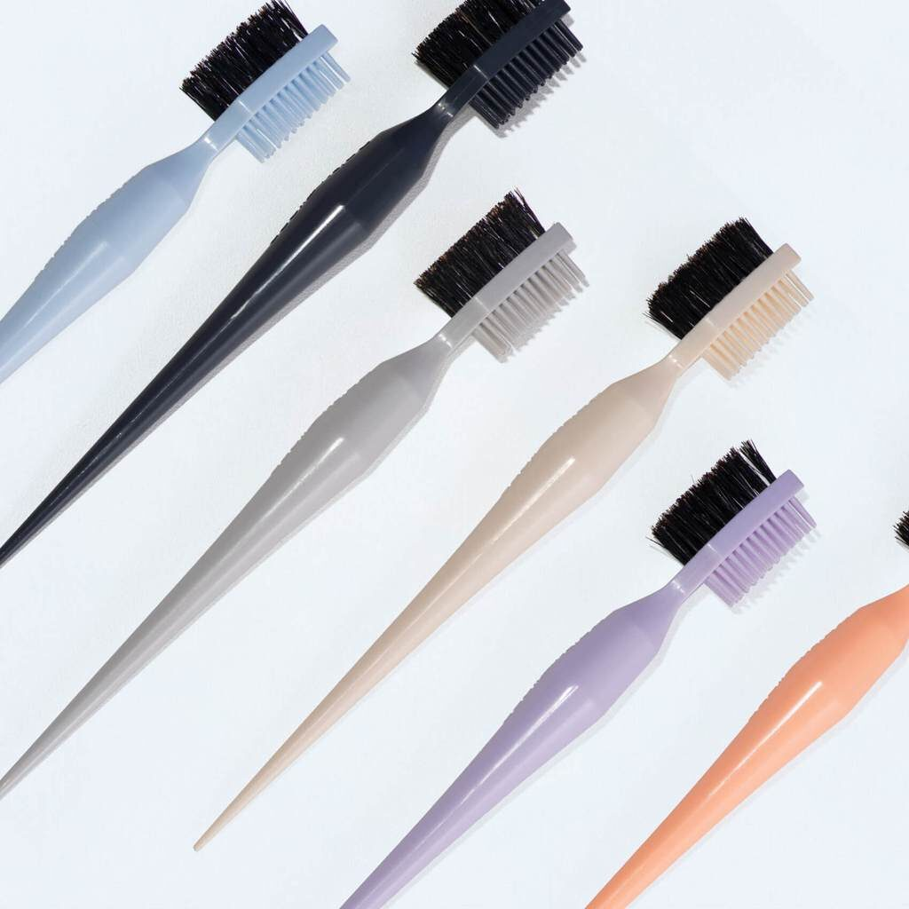 6 solid colored, but otherwise identical products, on a white background. The product has a double side brush - bristle board brush on side and a silicone brush on the other. On the bottom half of the product comes to point, that is used to separate hair. Product is from Baby Tress - a POC brand.