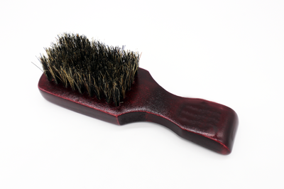 bristle boar brush with dark wooden handle and white background.