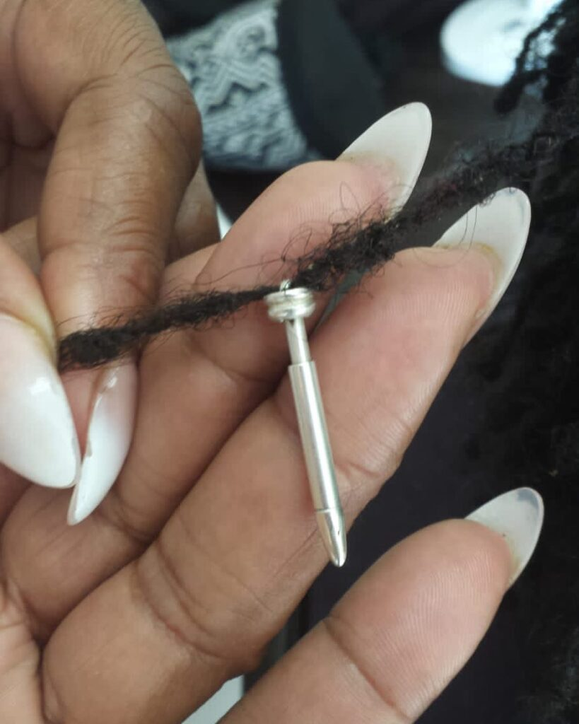 Black woman's hands in frame with long white nails holding a silver small interlocking tool with a loc in there. The interlocking tool is from a black owned business called Locks Royale.
