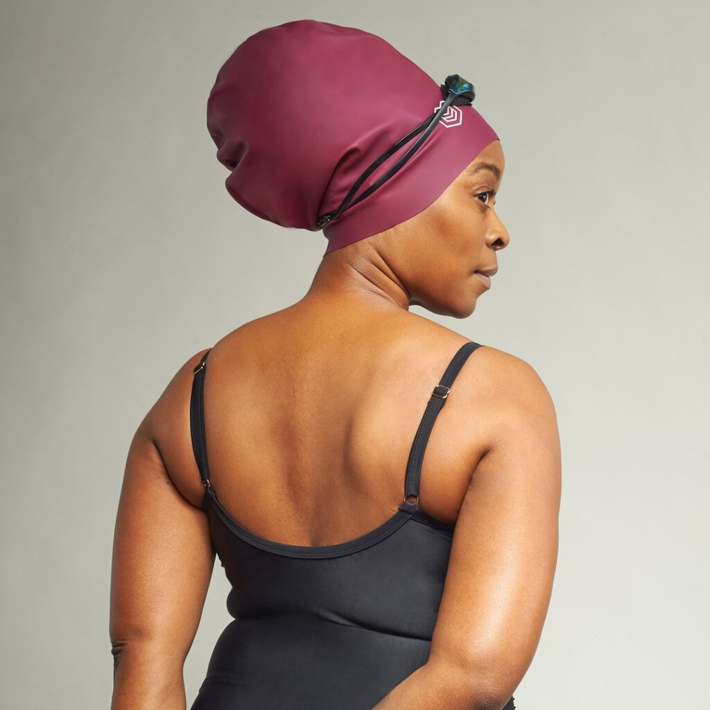 black woman with her back towards the camera and face to the side stands with one hand folded behind her back. She is wearing a black swim suit and a salmon red swim cap with googles on top. The swim cap is big enough to encompass the thick braids or perhaps locs that are within them. The swim cap is from a black owned brand called Soul Cap.