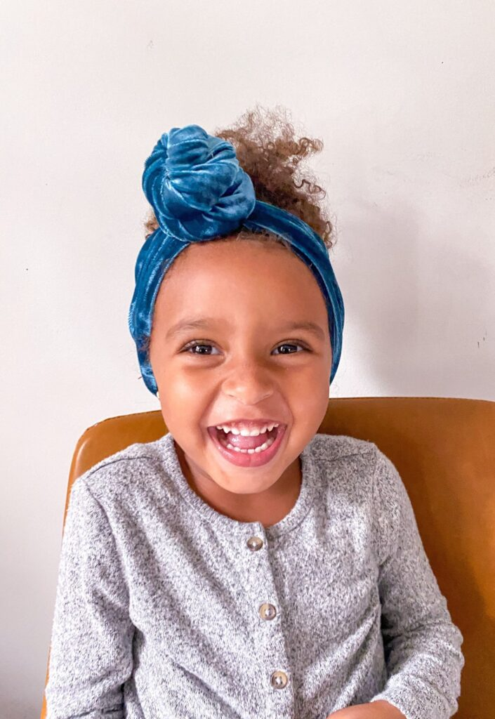 small child laughing/smiling infectiously at the camera wearing a tied knot blue turban from SweetMayCo, a black owned business. Child is wearing a grey Henley type shirt with buttons and is sitting on an orangey brown chair.